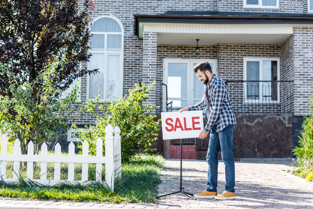 Man putting for sale sign up outside house