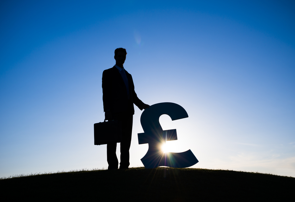 man standing on a hill with a pound sign next to him