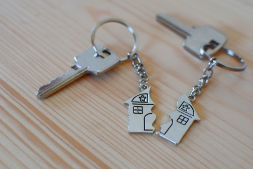 Pendant of key ring in shape of house divided in two parts on wooden background, closeup view. Selling house after divorce, division of property and real estate.