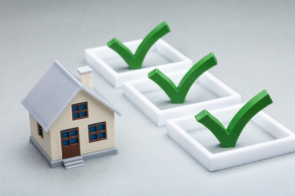 a model house next to 3 green ticks - a blog giving a house selling checklist.