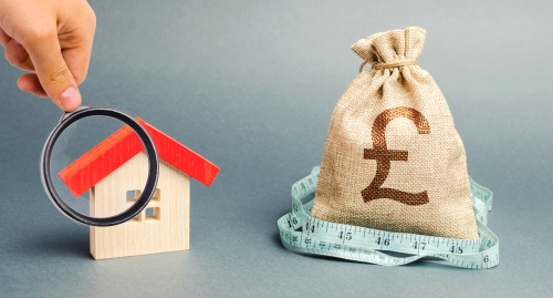 a house under a magnfying glass next to a money bag - house valuation concept.