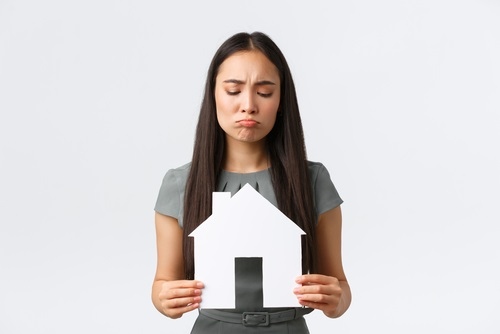 woman holding a paper house with sad face - house wont sell concept.