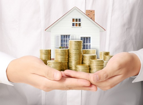 a man holding a house with coins in front. how to value your house concept.