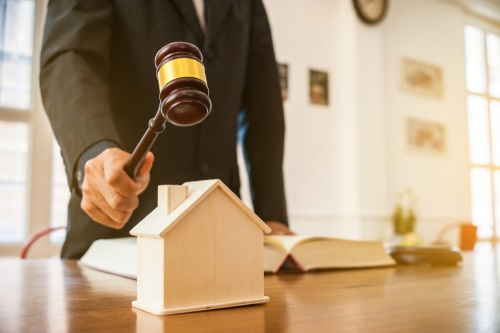 a gavel over a house - selling a house with legal problems concept.