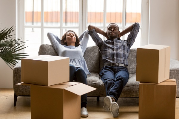 happy couple sitting on a sofa, having just sold their house - a post about house selling tips.