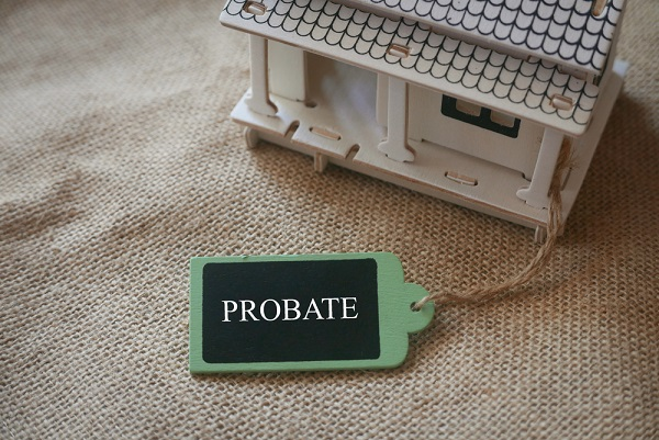 the word probate on a tag next to a toy wooden house - a blog about selling a house in probate